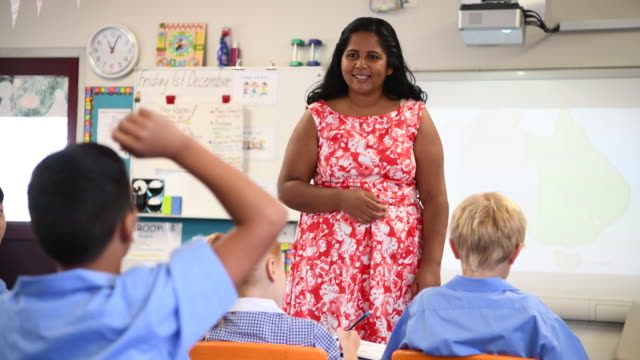 Aboriginal school teacher asking the class questions with a map of Australia on the whiteboard video