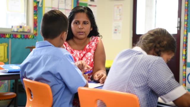 Aboriginal school teacher talking to school boy in classroom at desk video