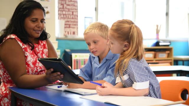 Aboriginal schoolteacher with digital tablet and schoolchildren video