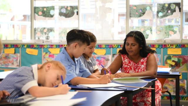 Aboriginal teacher helping children with their work in the classroom video