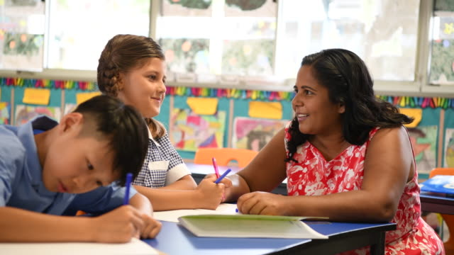 Aboriginal teacher smiling and talking to female pupil video