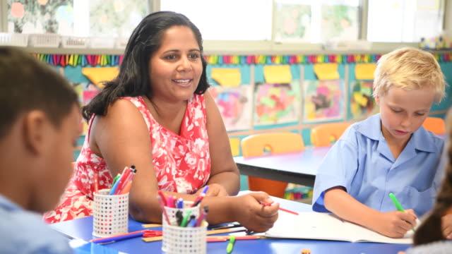Aboriginal teacher talking and smiling towards primary school children in art class video