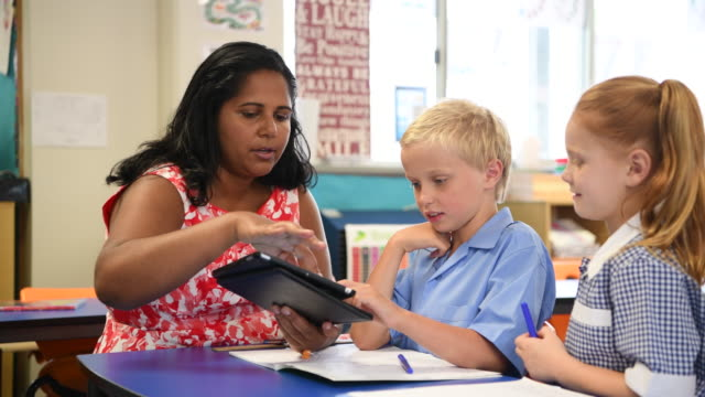 Aboriginal teacher using digital tablet with young boy and girl video