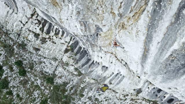 vídeos y material grabado en eventos de stock de antena sobre un escalador de roca femenina ascendente del acantilado - escalada en rocas