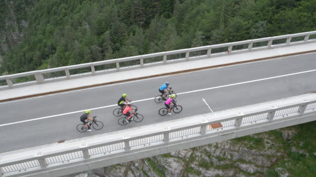 AERIAL Above a group of road cyclists riding across a viaduct