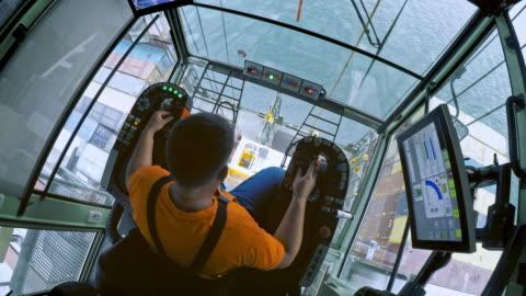 vídeos y material grabado en eventos de stock de ld por encima de un operador de grúa masculino mirando hacia abajo colocando un recipiente en el barco - experto