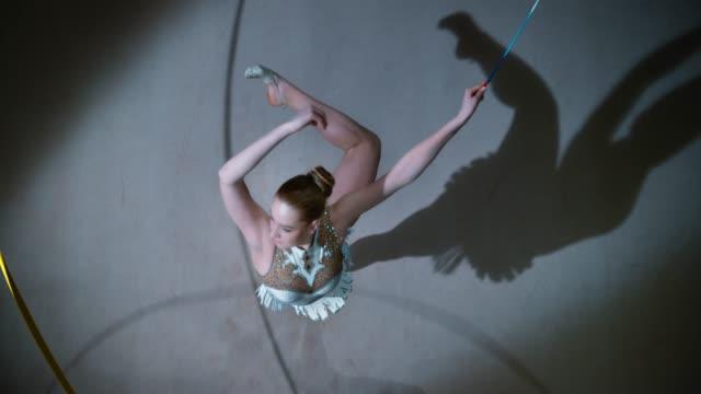 slo mo ld ovanför en rytmisk gymnast som utför en piruett med ett gyllene band i handen - piruett bildbanksvideor och videomaterial från bakom kulisserna