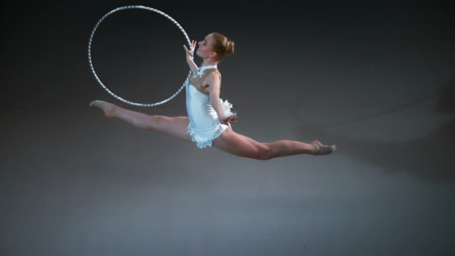 SLO MO LD Above a rhythmic gymnast performing a split leap while rotating her hoop in one hand