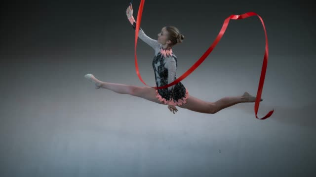 SLO MO SPEED RAMP LD Above a rhythmic gymnast performing a split leap while swirling a red ribbon