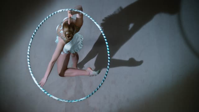 SLO MO LD Above a rhythmic gymnast pivoting while rotating a hoop above her head