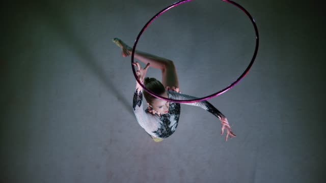 SLO MO LD Above a rhythmic gymnast pivoting while rotating a violet hoop above her head