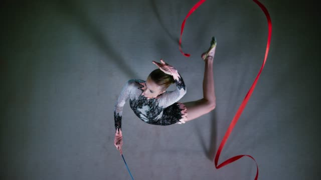 slo mo ld above a rhythmic gymnast pivoting while swirling her red ribbon - agilità video stock e b–roll