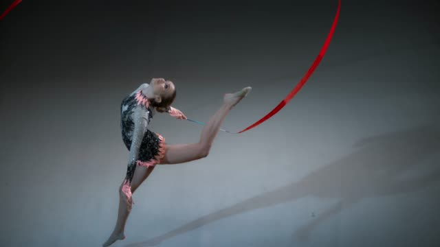SLO MO Above a rhythmic gymnast swinging a red ribbon above her head while performing a stag leap