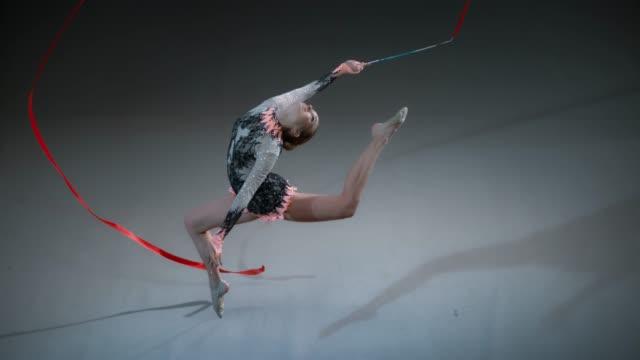 SLO MO SPEED RAMP LD Above a rhythmic gymnast swinging a red ribbon above her head while performing a stag leap