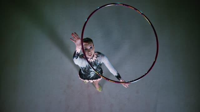 vídeos de stock, filmes e b-roll de slo mo ld acima de uma ginasta rítmica jogando um aro no ar e girando antes de pegá-lo - artista
