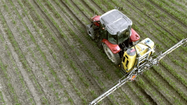 AERIAL Above a tractor spraying crops with a linkage sprayer video