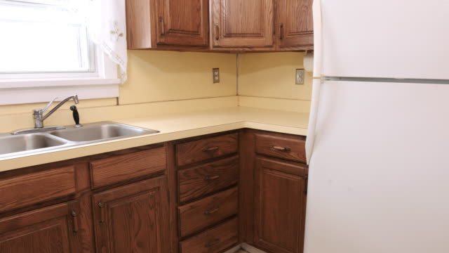Above Move In and Out Wide Shot of Old Yellow Kitchen Corner a medium wide shot of an out dated old yellow kitchen. Camera moves in and back cabinet stock videos & royalty-free footage