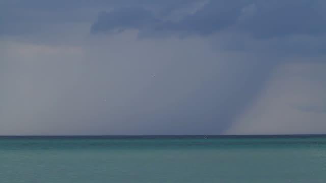 vídeos de stock e filmes b-roll de above the beach clouds gathered. - linha do horizonte sobre água
