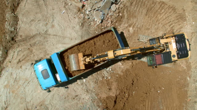 AERIAL Above the construction site with the excavator loading dug out soil onto a truck Aerial shot of the construction site with an excavator loading soil dug out at the site onto a truck. Shot in Slovenia. construction machinery stock videos & royalty-free footage