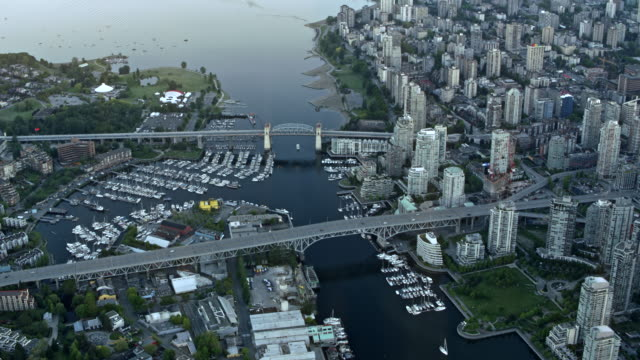 AERIAL Above the False Creek in Vancouver with Granville and Burrard Street Bridge Aerial shot of the False Creek in Vancouver with the Granville Bridge and the Burrard Street Bridge. Shot in Canada. vancouver canada stock videos & royalty-free footage