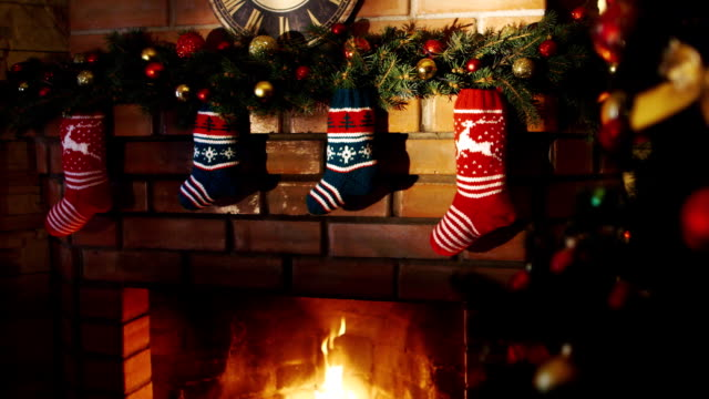 Above the fireplace hangs a burning socks for gifts for Christmas