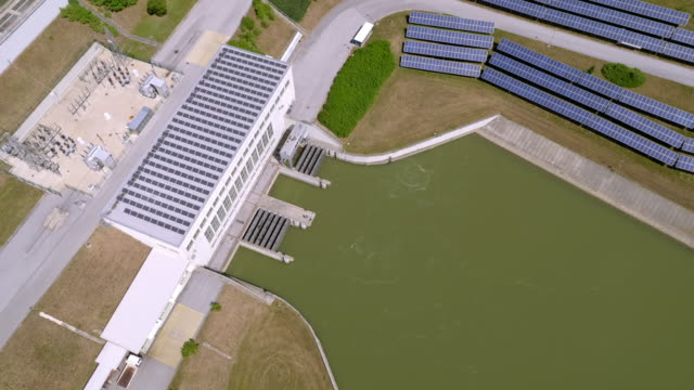 aerial above the hydropower plant zlatolicje with photovoltaic system - речной канал стоковые видео и кадры b-roll