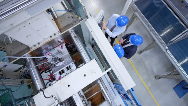 CS Above the male engineer and two buyer representatives discussing the control panel of the machine in the factory