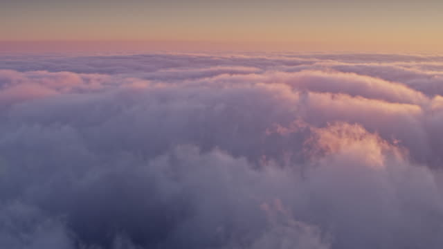 AERIAL Above the puffy clouds as the sun is setting