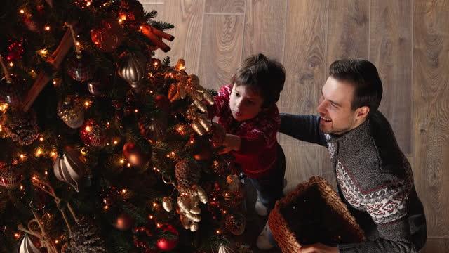 ovan visa glad far och liten son dekorera julgran - hänga bildbanksvideor och videomaterial från bakom kulisserna
