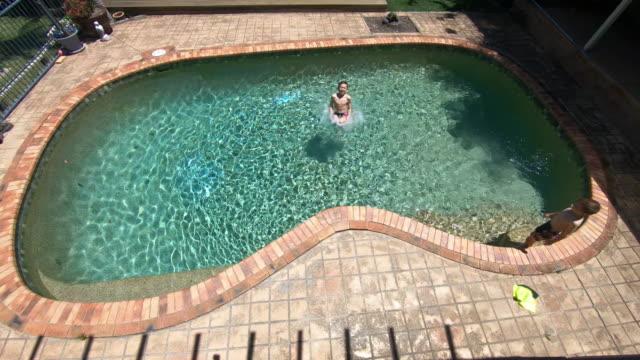 vídeos y material grabado en eventos de stock de por encima de la vista de un niño saltando en una piscina - backyard pool