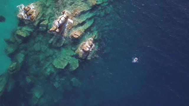 vídeos y material grabado en eventos de stock de por encima de la vista del pequeño barco que navegaba cerca de arrecifes - grecia europa del sur