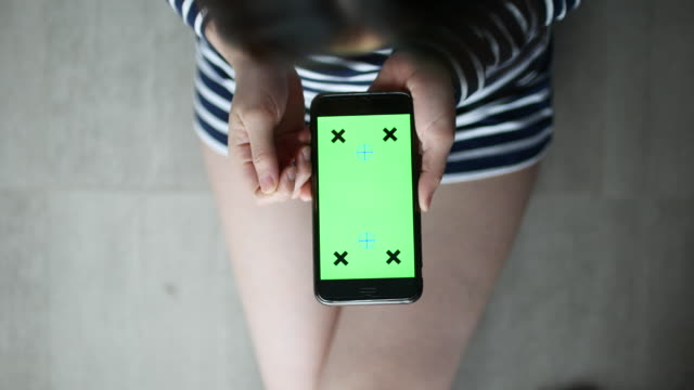 Above view of Woman Using Smartphone with Green screen video