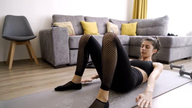 abs träning hemma. underbar kvinna gör abs övningar inomhus - working from home bildbanksvideor och videomaterial från bakom kulisserna