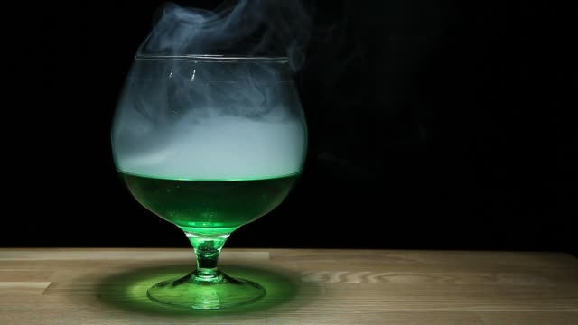 absinthe glass smoke wooden table hd footage nobody - narcotico video stock e b–roll
