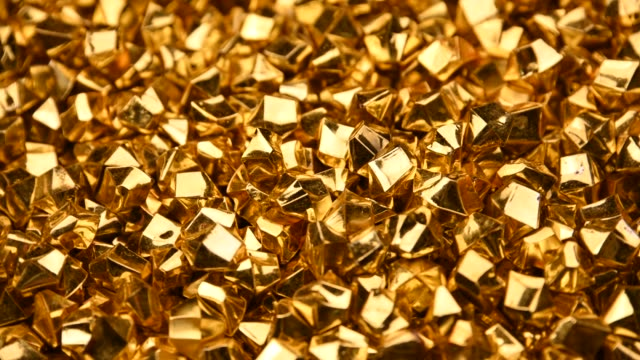 Abstract background of golden nuggets spinning