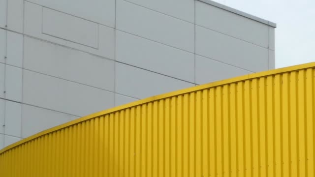 Abstract background yellow metal white concrete blue sky. Panoramic shot. Pan shot of an abstract background. Yellow metal and grey white concrete on factory building. Panoramic shot moving from left to right. yellow stock videos & royalty-free footage