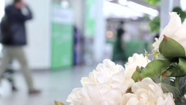 Abstract blur beautiful modern luxury shopping mall and retails store interior for background, people walking in shopping mall, beautiful white flowers on foreground
