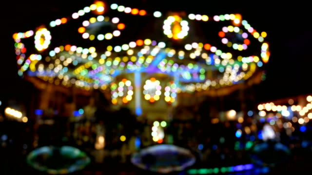 4K. abstract blur children's merry-go-round carousel at night with bokeh light on festival for background video