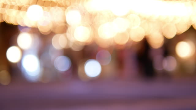 Abstract blurred bokeh background of festival decorative string lights hang and glow outdoors at night with blurrry people moving in festive Christmas market festival.