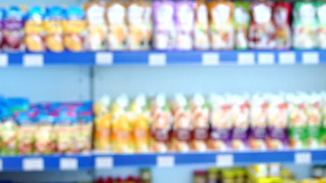 vídeos de stock e filmes b-roll de abstract blurred supermarket with various products on the shelves. - bebida fresca