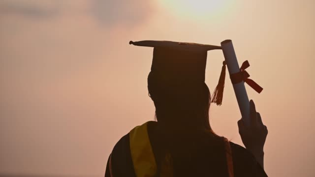 abstract close up rear view of the university graduates at silhouette sunset - tocco accademico video stock e b–roll