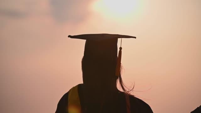 vídeos de stock, filmes e b-roll de resumo close-up visão traseira dos graduados universitários no pôr do sol silhueta - beca