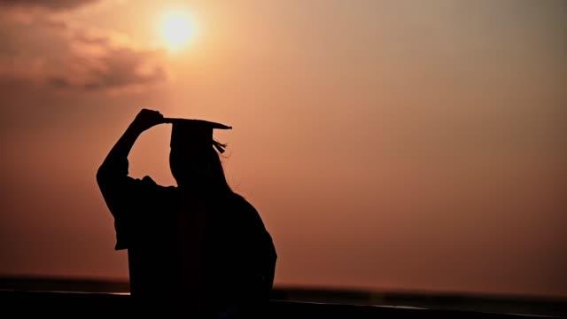 vídeos y material grabado en eventos de stock de abstracto vista trasera de cerca de los graduados de la universidad en silhouette puesta de sol - graduación