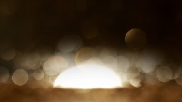 abstract golden bokeh background with big size sun down on ocean water - bokeh stock videos & royalty-free footage