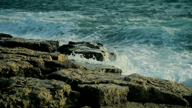 Abstract large sea waves beautifully splash on the rocks on the beach in slow motion. video