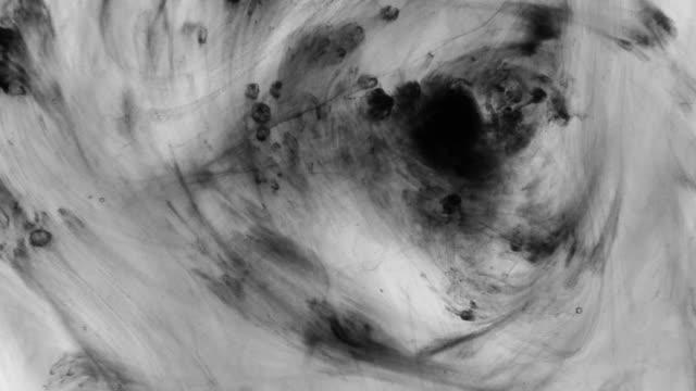 Mouvement abstrait de peinture noire et blanche dans l'eau. Vue d'en haut. - Vidéo