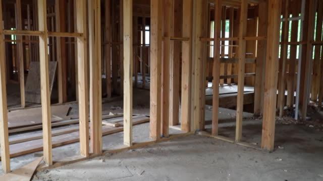vídeos de stock e filmes b-roll de abstract of wood home framing at construction site. building frame structure on a new development - obras em casa janelas