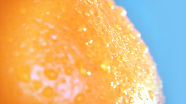 Abstract organic background. Rotating orange with droplets macro. HD video
