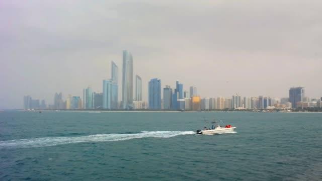 abu dabi şehir silüeti, şehir simge yapılarına ve sahilde bir tekne gezisi ile güzel görünümü - abu dhabi stok videoları ve detay görüntü çekimi