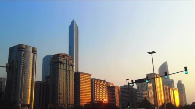 abu dabi şehir manzarası kuleleri altın saat gün batımında - corniche görünümü göster - abu dhabi stok videoları ve detay görüntü çekimi